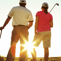 Man and woman golfing at sunset